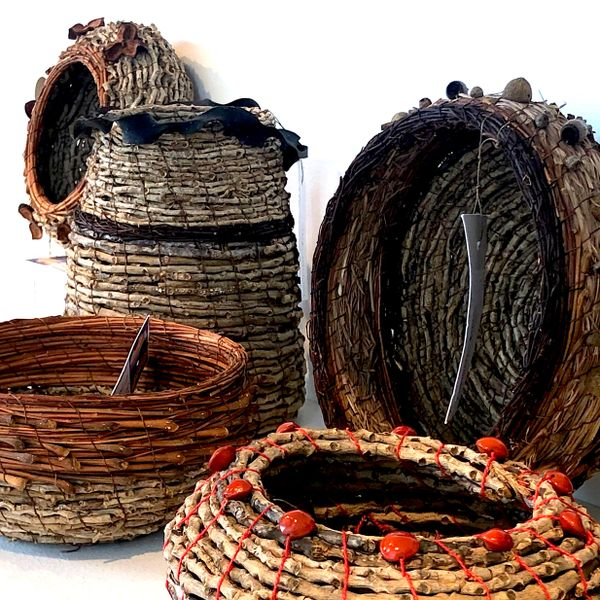 A collection of hand woven natural fibre baskets sitting on a white shelf in the window of Object Shop.
