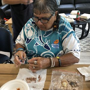 A woman with brown skin and long grey hair looking intently at small jewellery parts with pliers in her hand.