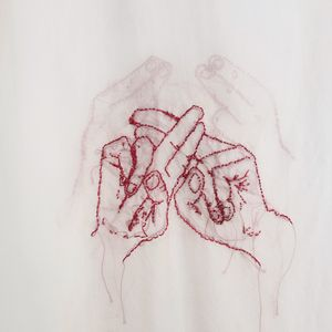 Two hands forming the ASLAN sign for family stitched in red on white fabric