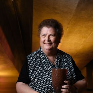 Photo of a senior woman with curly hair with award with designed wooden background at Sydney Opera House.