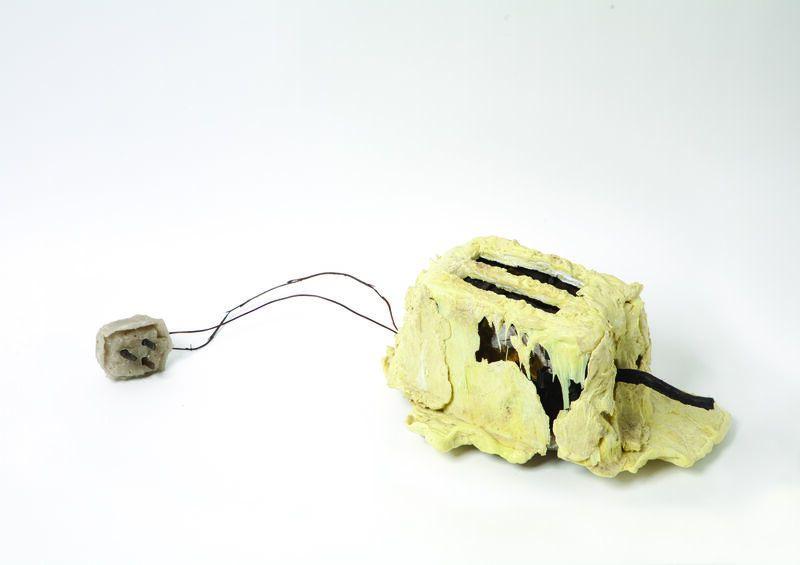photo of a melted yellow looking toaster on a grey background.
