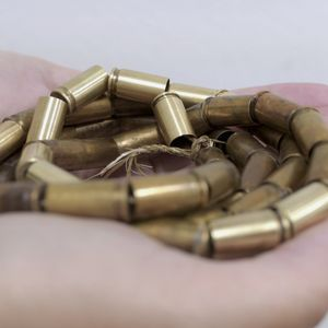 Brass Bullet casings threaded together and held in a persons palm