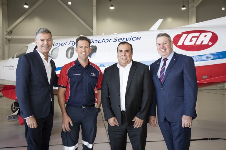 3 people smile at the camera. They are stood in front of an aircraft with RFDS logo. There is one female and two males.