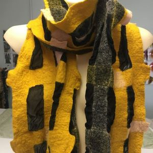 A mustard and black felted scarf wrapped around a mannikin.