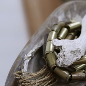 Threaded brass bullet cases arranged on a shell with a piece of driftwood