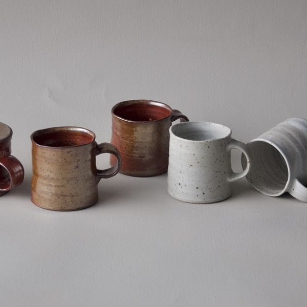 A group of five mugs some with brown shino glaze, some with white speckled glaze