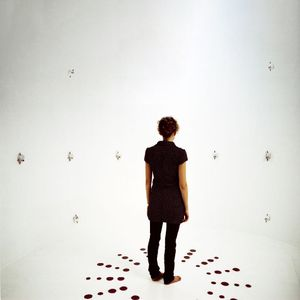 Someone standing in the middle of an empty room with blank white walls and surrounded by tiny cameras.