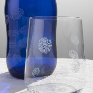 A close up image of a clear glass and blue bottle with engraved fingerprints on the surface