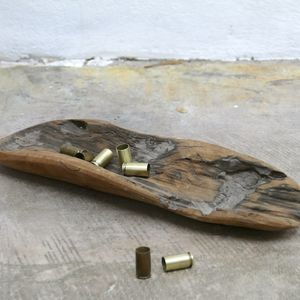 Brass bullet casings placed within a wooden wirri and placed on the ground
