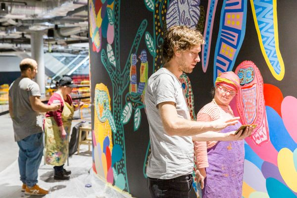 An artist from Studio A working on a detail of the wall painting, 'Bird Life Jungle Disco'