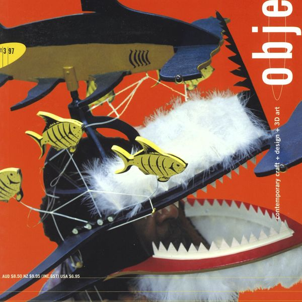 Magazine cover with a make figure wearing a Shark Dance Mask on a red background