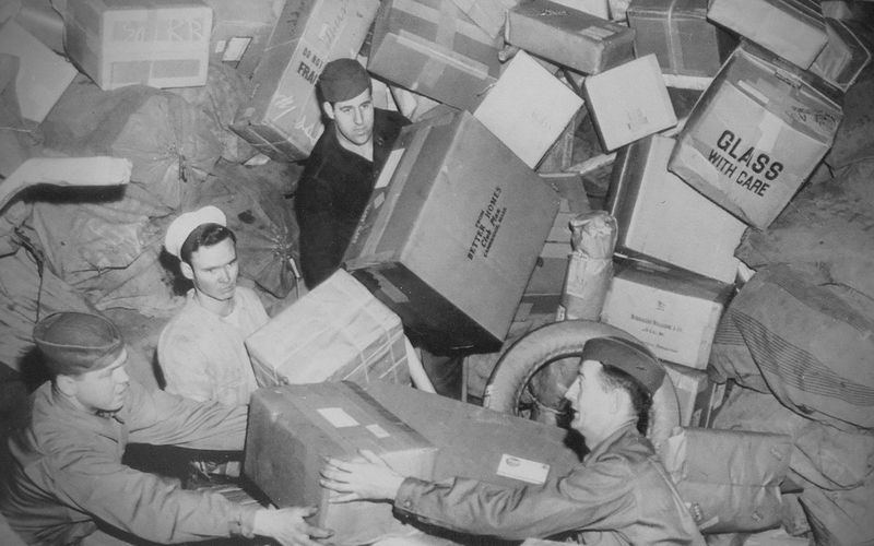 Three U.S. soldiers being almost buried by parcels at a mail depot during World War 2, circa 1944