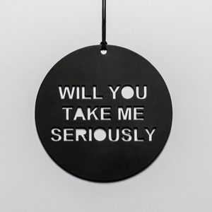 """Black circular metal disk with the words """"Will you take me seriously"""" cut out"""
