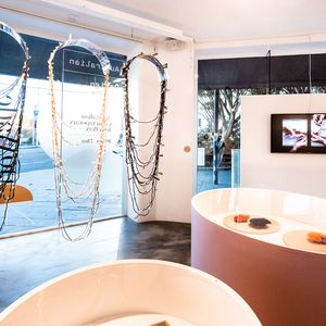 Photo inside gallery with concrete floor with coloured plinths for contemporary jewellery exhibition.