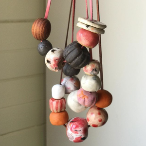 Three brightly coloured ceramic bead necklaces hanging in a bundle against a white background