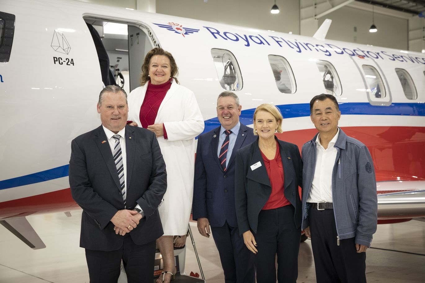 5 adults smile at the camera. They are all wearing corporate attires. An aircraft with RFDS logo and S Kidman and Co logo is behind them.