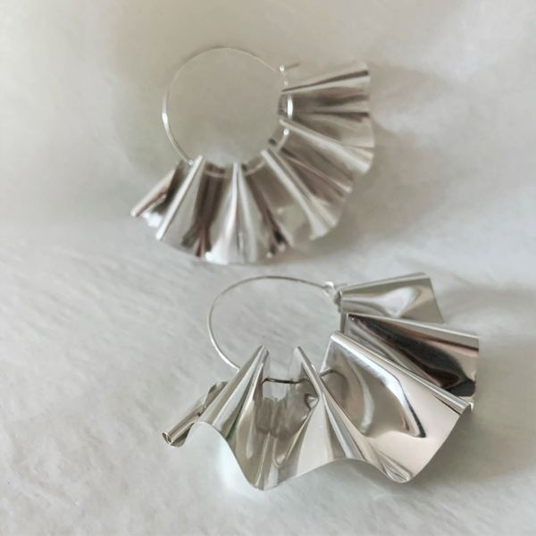 A pair of shiny rippled sheet silver earrings on silver hoops, on a white background.