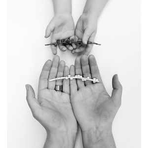 Photograph of hands holding a dried Callistemon and a white metal pendent of a Callistemon