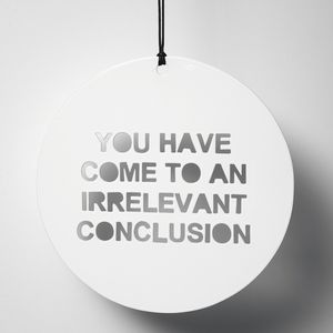 """White circular metal disk with the words """"YOU HAVE COME TO AN IRRELEVANT CONCLUSSON"""" cut out"""