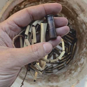 Hand holding reeds and bullet casings