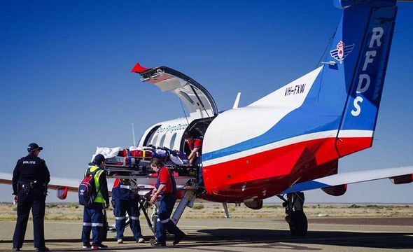 Man attending to patient next to plane