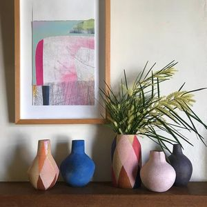 Five brightly coloured ceramic vessels standing on a side table underneath a colourful framed artwork.