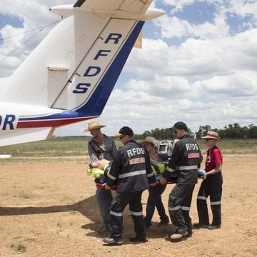 Injured stockman lays on ground with RFDS treating him