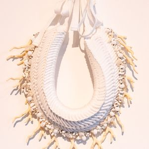 photo of a woven fabric circular shape with bead and corals sewn into it