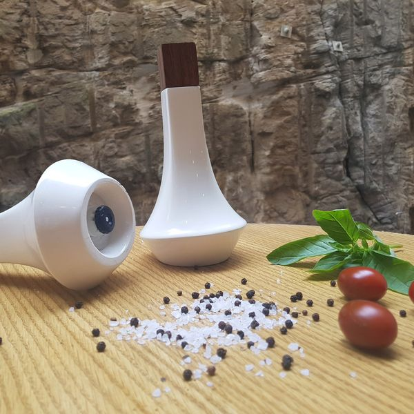 White ceramic and wood salt and pepper shakers, with salt, pepper, tomatoes and basil leaves scattered nearby.
