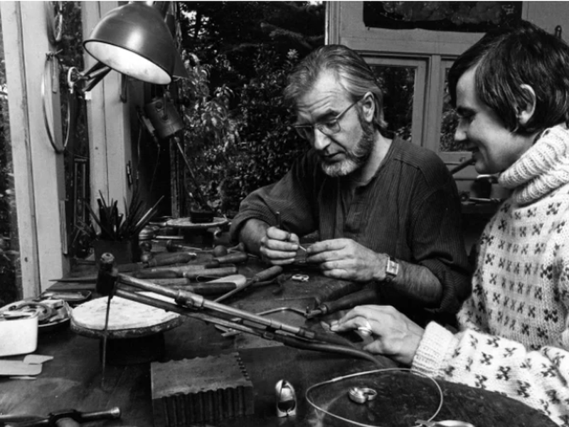 Black and white photo of a man with beard and woman with short hair in a jewellery studio looking closely at a work