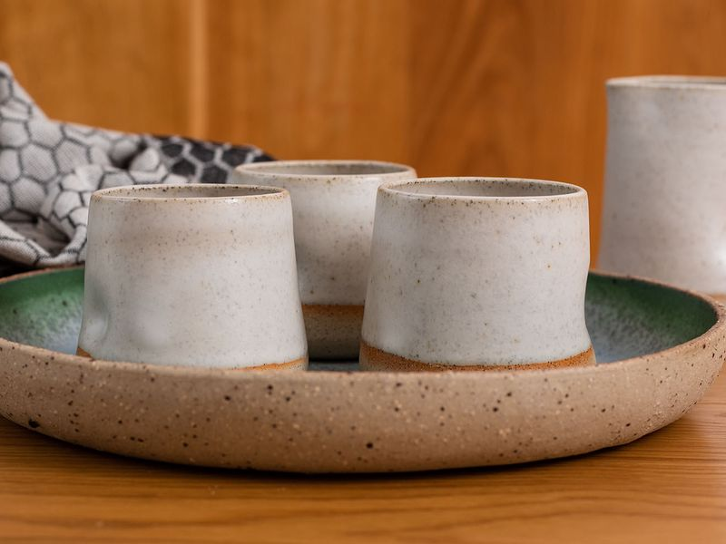 Photo of handmade ceramic mugs in  creamy beige colour on a platter with a wooden background.