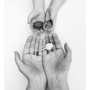 Photograph of hands holding a dried Gumnut and also a white metal pendent reinterpreting the Gumnut