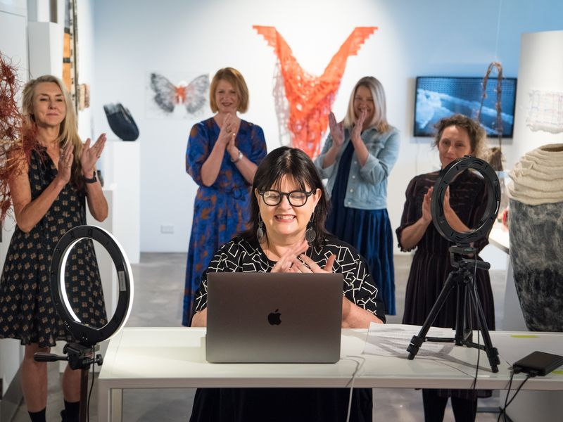 Photo of a woman with lights speaking into a computer for a zoom opening with four women standing  behind in a gallery space.