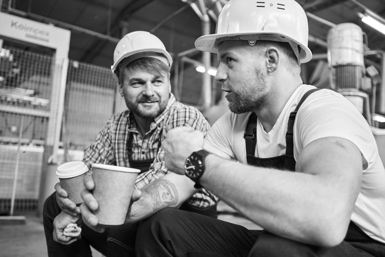 Two men chatting whilst holding cups of tea.
