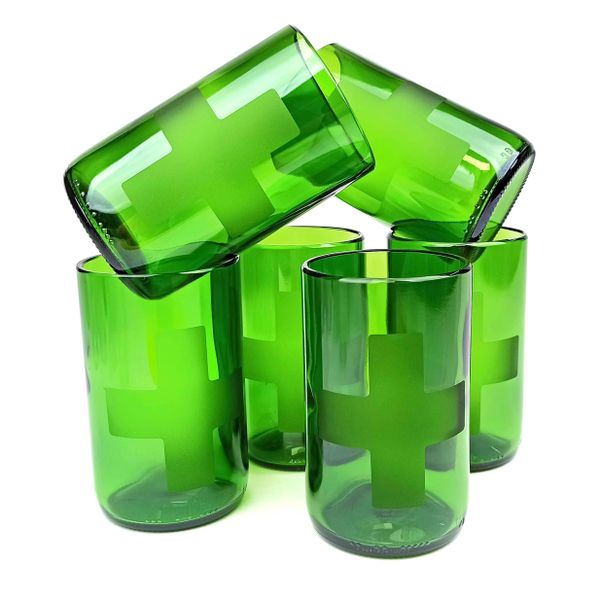 A stack of green glass recycled tumblers with a cross design etched into the side of each glass