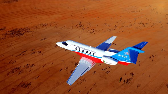 A jet aircraft with RFDS logo flies over a dry, brown landscape