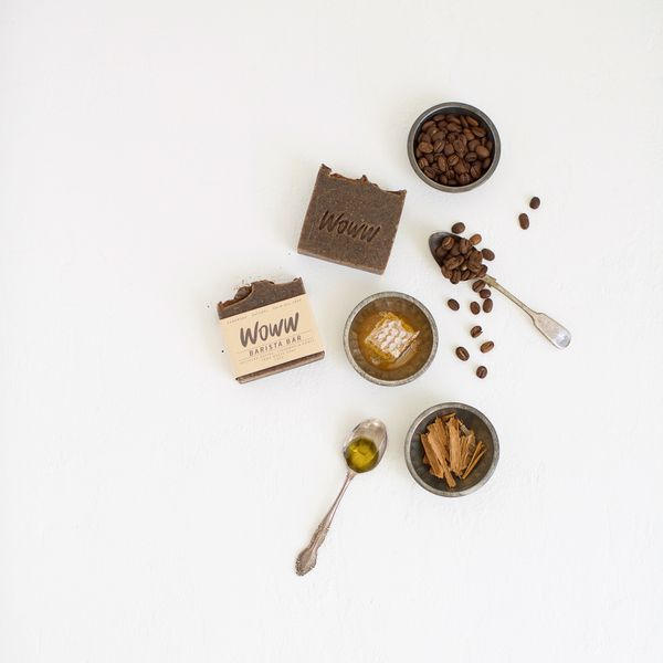 Hand-made soap surrounded by mixing spoon, dishes, coffee beans, honey, cinnamon sticks.
