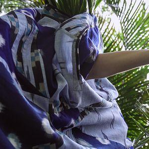 Figure in movement wearing flowing blue dress amongst green Palm leaves
