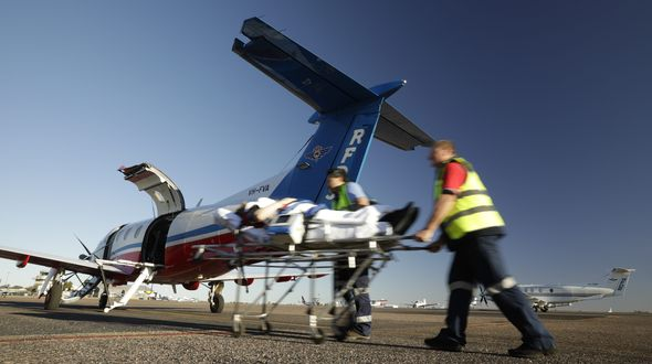 Two men in RFDS uniforms push a stretcher towards a RFDS plane.