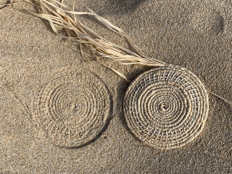 Melinda Young, Thinking/making - an impression in the sand, Woven component, Raffia and found string. 31 March 2020