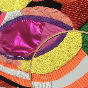 Close up image of colourful beaded embroidery in progress