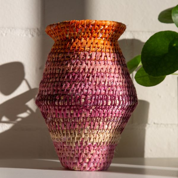 A brightly coloured woven basket sitting on a windowsill.