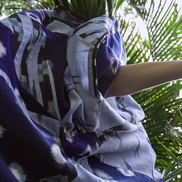 Figure in movement wearing flowing blue dress amongst green Palm leaves
