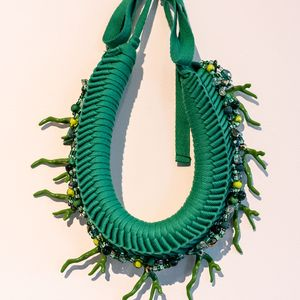 photo of a fabric circular woven neckpiece with bead sewn in
