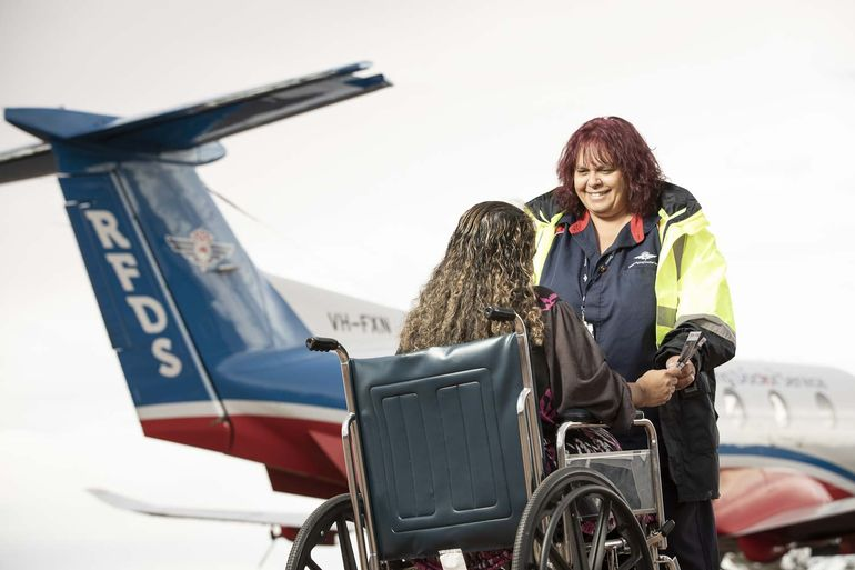 A lady is sat in a wheelchair. She holds hands with a lady in RFDS uniform, they are smiling. A RFDS aircraft is in the background.