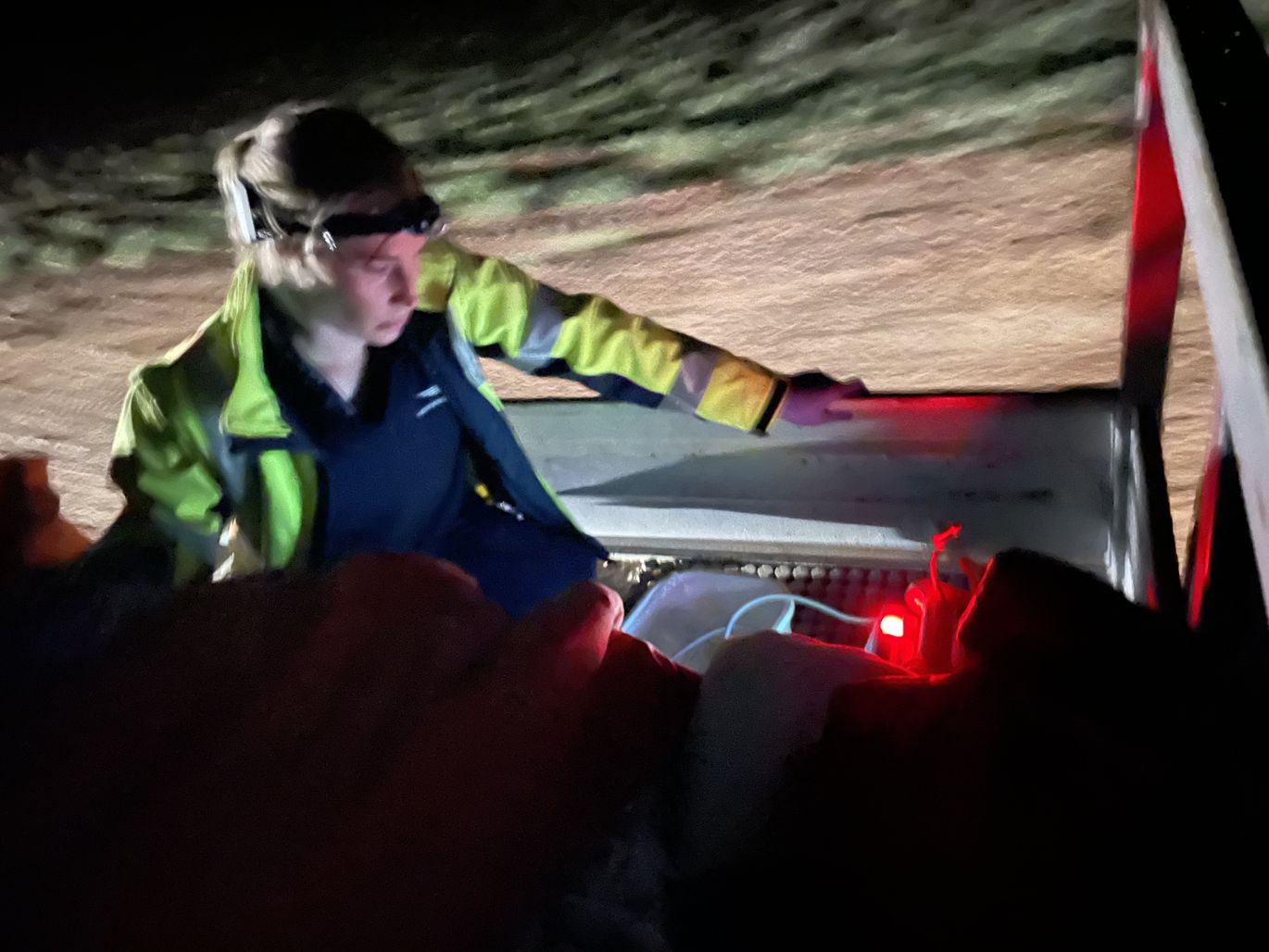 Dr Jess Martyn rides on the back of a ute, transporting Shirley to the aircraft