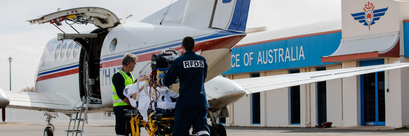RFDS Doctors loading a patient into an RFDS Plane.