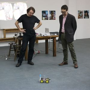 Josh Harle and another person observing a wheeled robot on the ground.